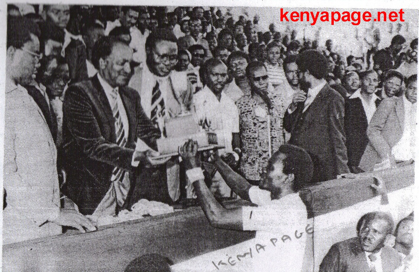 Andrew Obunga receives cup from minister Jeremiah Nyaga